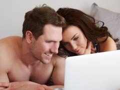 Flirtatious swinging couple using laptop computer to access chat and webcam rooms